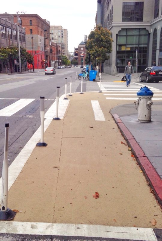 Proposed: Painted safety zones with flexible delineator posts.